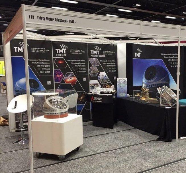 国際光工学会(SPIE)におけるTMTブース展示。日本から提供したTMT全体の模型(左手前)と主鏡分割鏡交換機構の模型(中央)も展示されました。
