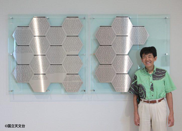 3906名のお名前が刻まれた寄付者銘板の傍らに立つ臼田TMT推進室長。第三期銘板は左側から4列目の一番下(1枚)と5列目(3枚)、第四期銘板は6列目(4枚)と7列目(1枚)です。